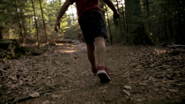 stockvideo's en b-roll-footage met detail dat van een jonge jongen is ontsproten loopt in het bos - hoofddeksel