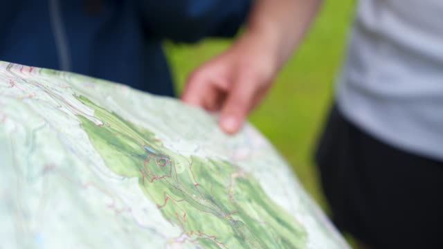 detail shot of hikers looking at a map - karte navigationsinstrument stock-videos und b-roll-filmmaterial