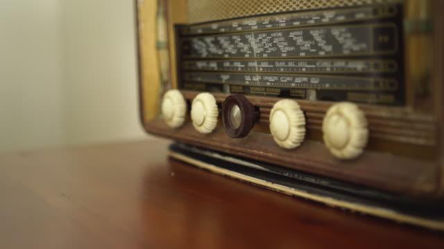 scatto dettagliato di qualcuno che accende una vecchia radio - accendere e spegnere video stock e b–roll