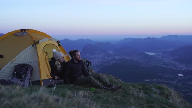 vídeos y material grabado en eventos de stock de detalle de dos excursionistas tomando una selfie al atardecer en la cima de una montaña - tienda de campaña