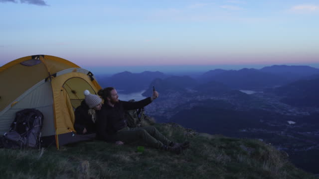 detail shot of two hikers taking a selfie at sunset on top of a mountain - young men stock videos & royalty-free footage