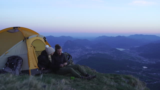 detail shot of two hikers taking a selfie at sunset on top of a mountain - camping stock videos & royalty-free footage