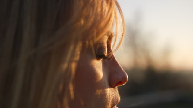 detail shot of woman's eye, her hair blowing in the wind while she meditates - sunlight stock videos & royalty-free footage