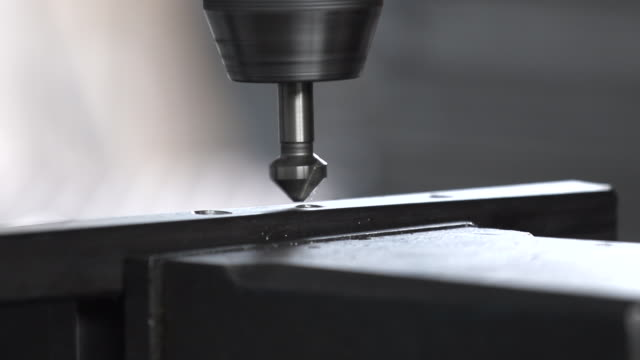 Detail steel bars being drilled by a drill press to create a structure in a machine shop.