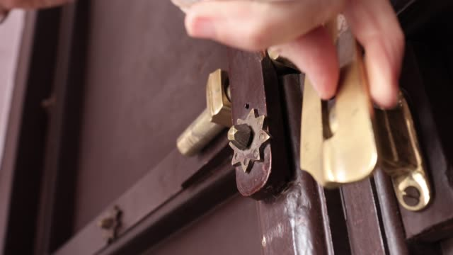detail view of woman closing door, applying lock - arte dell'antichità video stock e b–roll
