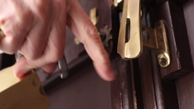detail view of woman closing door, applying lock - lock stock videos & royalty-free footage