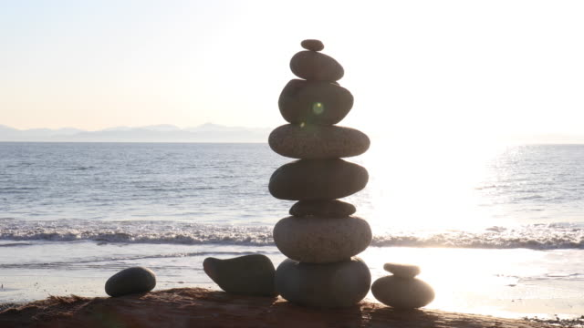 detail view of zen rock stack on beach at sunrise - surf rock stock videos & royalty-free footage