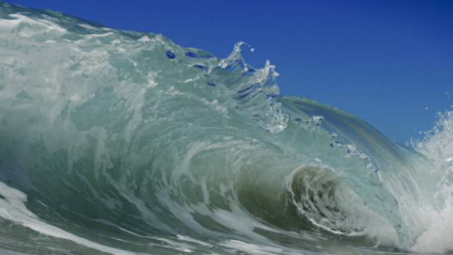 a detailed beautiful wave breaks over camera in pov on shallow sand beach in the california summer sun. shot in slow motion on the red dragon at 150fps in 4k. - surf stock videos & royalty-free footage