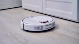 Detailed view on a self-moving robotic vacuum on the floor.