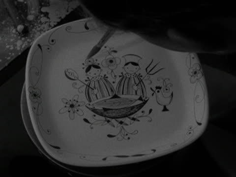 details are painted onto a patterned plate at the stavanger pottery workshop. 1959. - stavanger stock videos & royalty-free footage