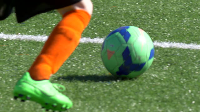 details of a ball and boys legs playing youth soccer football on a turf field. - human limb stock videos & royalty-free footage