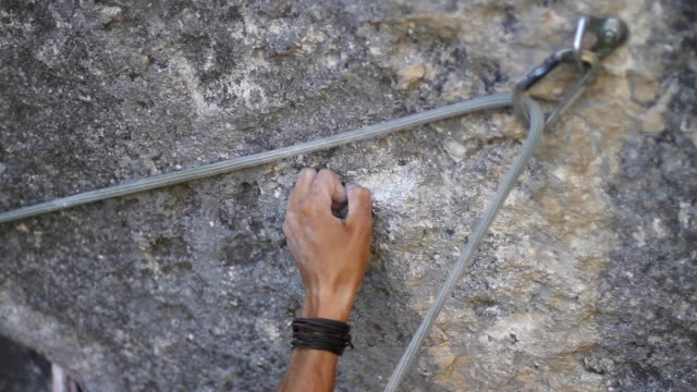 details of a man rock climbing up a mountain and his hand holding on. - entschlossenheit stock-videos und b-roll-filmmaterial