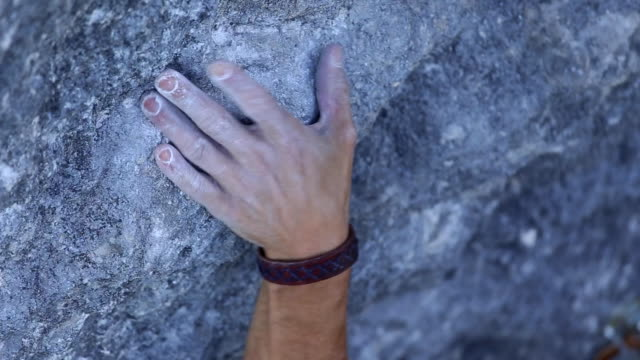 Details of a man rock climbing up a mountain and his hand holding on.