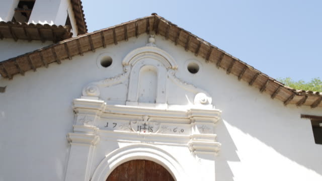details of houses that are used as a community college calera de tango chile the letters ihs are written above the door the door and roof are made of... - jesuit stock videos and b-roll footage