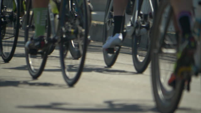 details of men racing in a road bike bicycle race. - slow motion - プロトン点の映像素材/bロール