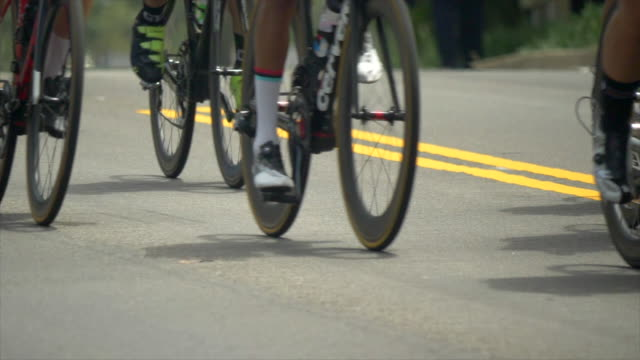 details of men racing in a road bike bicycle race. - slow motion - ロードサイクリング点の映像素材/bロール