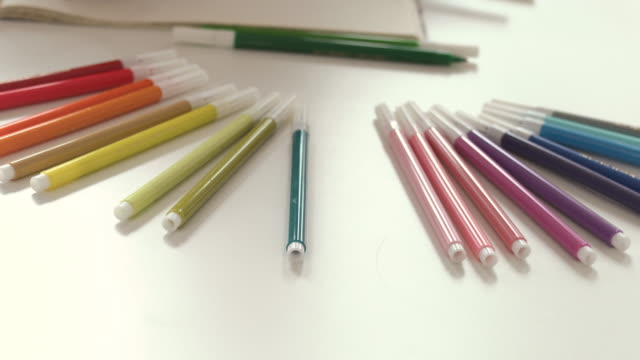 Details of pens and coloring book on the table