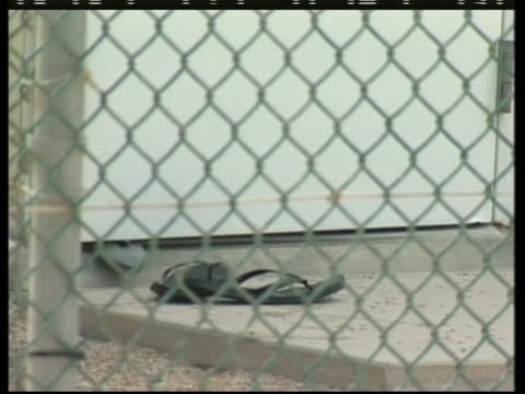 a detainee at the camp delta section of guantanamo bay removes his sandals before stepping inside - crime or recreational drug or prison or legal trial stock-videos und b-roll-filmmaterial