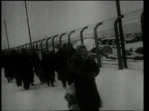 vídeos de stock e filmes b-roll de detainees marching through snow past barbed wire fence / auschwitz, germany - nazismo