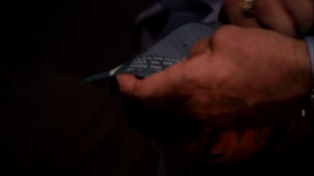 a detective attaches a strap to a suspect's tattooed arm. - sospetto video stock e b–roll