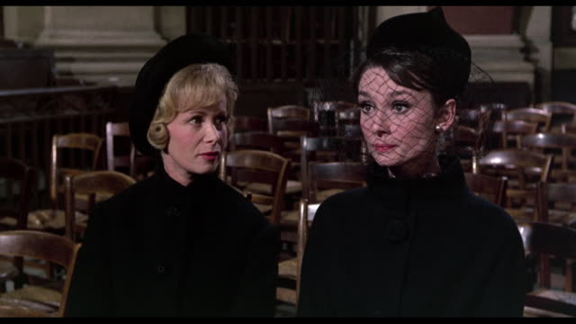 1963 detective (jacques marin) clips his nails as woman (audrey hepburn) talks to friend at a desolate and empty funeral service - teilnehmen stock-videos und b-roll-filmmaterial