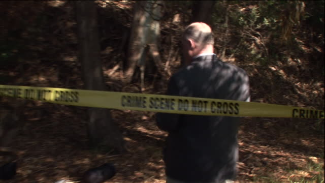 vídeos y material grabado en eventos de stock de a detective crosses crime scene tape to investigate a wooded area. - detective