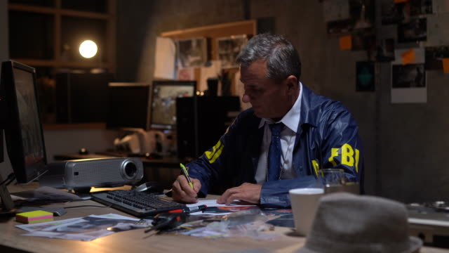 vidéos et rushes de détective de fbi faisant la paperasse - paperasserie