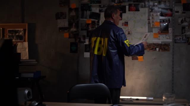 vídeos de stock, filmes e b-roll de detetive do fbi na frente da parede com evidências - pilot