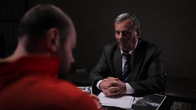 detective interrogating a prisoner in interrogation room - prisoner orange stock videos & royalty-free footage