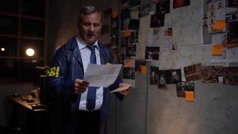 fbi-detektiv liest beweise und löst ein verbrechen - fbi stock-videos und b-roll-filmmaterial
