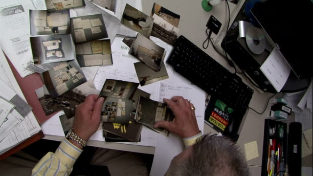 a detective reviews a photograph of a crime scene. - detektiv stock-videos und b-roll-filmmaterial