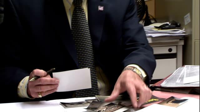vídeos y material grabado en eventos de stock de a detective reviews photographs in his office. - detective