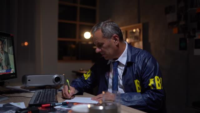 vidéos et rushes de détective de fbi utilisant l'ordinateur - document