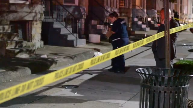 detectives and crime scene investigators look for clues after multiple people were shot at the jermaine scofield candlelight vigil five people were... - verbrechen stock-videos und b-roll-filmmaterial