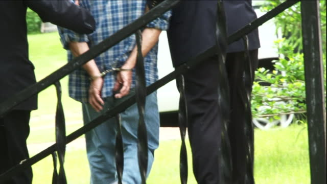 detectives escort a suspect across a lawn. - suspicion stock videos & royalty-free footage