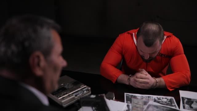detektive verhören einen männlichen häftling im dunklen raum - akte stock-videos und b-roll-filmmaterial