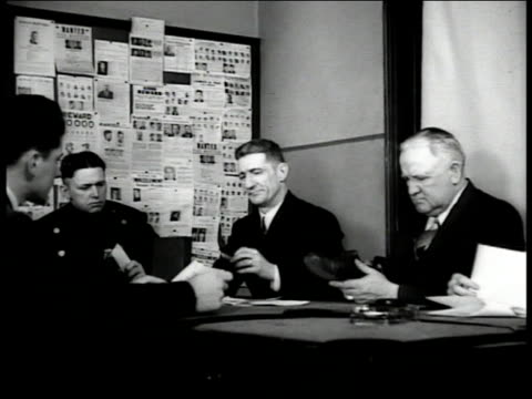 'Detectives Room' sign on door Detectives seated at table looking over papers holding shoe evidence CU Set of single finger print above below pencils...