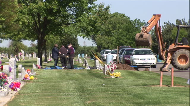 detectives stand above an exhumed grave. - gravestone stock videos & royalty-free footage