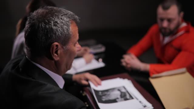detektive sprechen mit häftling im verhörraum - befragung stock-videos und b-roll-filmmaterial