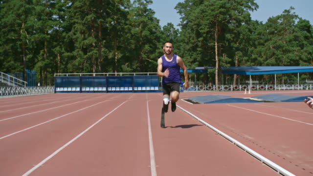 determined amputee runner training for paralympics - amputee stock-videos und b-roll-filmmaterial