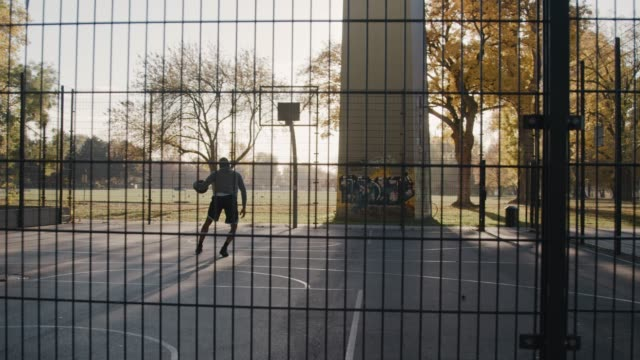 ermittelten sportler spielen am basketballplatz - zaun stock-videos und b-roll-filmmaterial