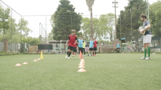 determined boys and girls practicing soccer drills on field - boys stock videos & royalty-free footage