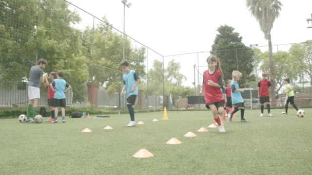 determined boys and girls practicing soccer drills on field - sweat stock videos & royalty-free footage