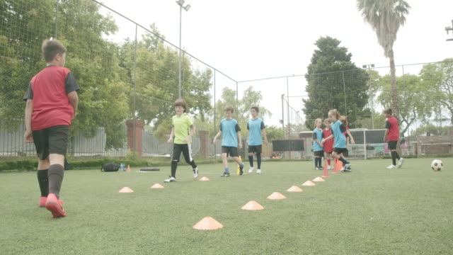 determined boys and girls practicing soccer drills on field - sports training drill stock videos & royalty-free footage