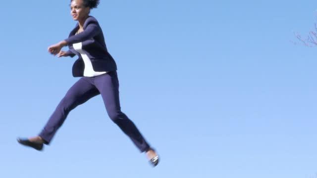 vídeos y material grabado en eventos de stock de decidida empresaria saltando - traje