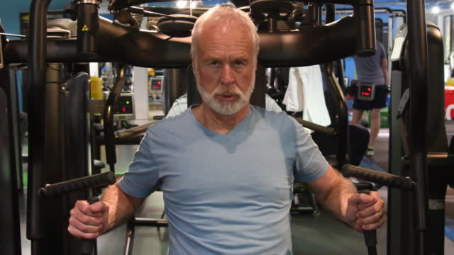 determined caucasian male working on upper body strength at gym - retirement stock videos & royalty-free footage