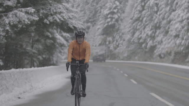 stockvideo's en b-roll-footage met determined female athlete riding bicycle on highway during snowfall - bevroren