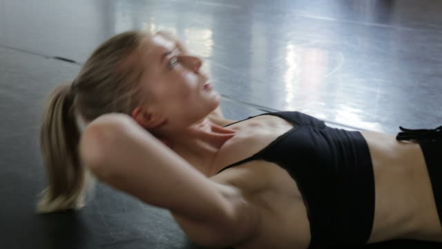 Determined female ballet dancer doing sit-ups in rehearsal room