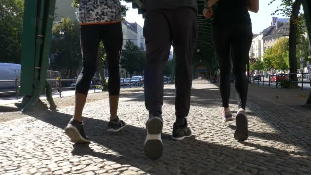 Determined friends jogging under bridge