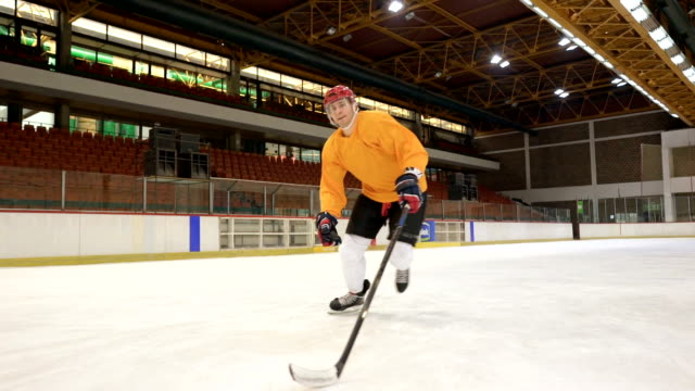 determined ice hockey player tackling and shooting at goal during sports training in a rink. slow motion. - ice hockey stock videos and b-roll footage
